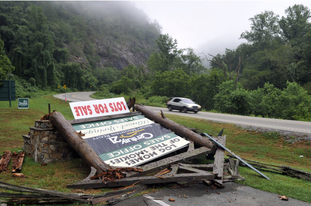 A sign advertising lots for sale lies in pieces on the ground in the Kinzel Springs community Friday, July 6, 2012, near Townsend, Tenn., following a violent storm that swept through nearby Great Smok