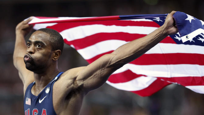 FILE - In this Aug. 16, 2009 file photo, United States' Tyson Gay who placed second celebrates with the U.S. flag after the Men's 100m final during the World Athletics Championships in Berlin. Gay said Sunday, July 14, 2013 that he tested positive for a banned substance and that he will pull out of the world championships next month in Moscow. (AP Photo/Anja Niedringhaus, File)