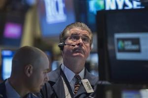 Trader Daniel Kryger looks up at a screen while working on the floor of the New York Stock Exchange
