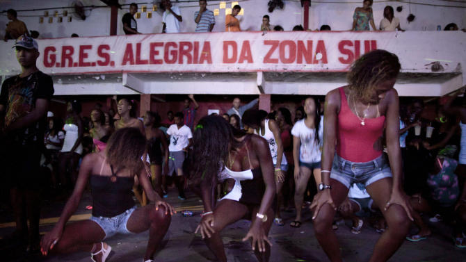 "In this Feb. 3, 2012, women dance during a funk ""baile,"" or party, in the Cantagalo slum in Rio de Janeiro, Brazil. Its market potential has become hard to ignore: A recent survey by the Brazilian think tank the Getulio Vargas Foundation found funk disc jockeys, MCs and others generate about $720 million a month in revenue. (AP Photo/Felipe Dana)"