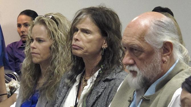 Aerosmith lead singer Steven Tyler, center, sits with his attorney Dina LaPolt, left, and Fleetwood Mac drummer Mick Fleetwood as they listen to testimony on a celebrity privacy bill during a hearing at the Hawaii Capitol in Honolulu on Friday, Feb. 8, 2013. Rock legends Steven Tyler and Mick Fleetwood convinced a Hawaii Senate committee on Friday to approve a bill to protect celebrities or anyone else from intrusive paparazzi. The state Senate Judiciary Committee approved the so-called Steven Tyler Act after the stars testified. The bill would give people power to sue others who take photos or video of their private lives in an offensive way. (AP Photo/Oskar Garcia)