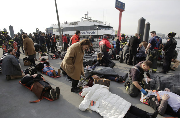 Victims of the Seastreak Wall Street ferry accident are aided by rescue personnel, Wednesday, Jan. 9, 2013 in New York. The ferry, rear, from New Jersey made a hard landing at the dock as it pulled up