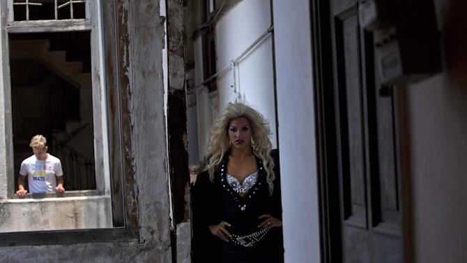 """Gay artist Gilberto Diez, 18, right, a transvestite gay artist known as """"Ashenal,"""" walks down a hallway as his companion Ernesto Nogues, 22, is seen through an open window, standing in his home in Havana, Cuba, Thursday, May 16, 2013. A week of drag shows, colorful marches and social and cultural events in Havana culminates Friday with celebrations of the International Day Against Homophobia. Gays were persecuted for decades after the 1959 Cuban Revolution, sometimes sent to grueling rural work camps along with others considered socially suspect by the Communist government. But there has been a gradual shift away from macho attitudes, and Fidel Castro himself has publicly regretted the mistreatment of people seen as different. (AP Photo/Ramon Espinosa)"""