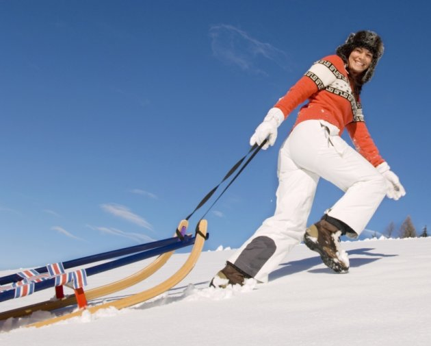 Woman pulling a tobaggan sled up a hill