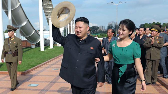 FILE - In this July 25, 2012 file photo released by the Korean Central News Agency (KCNA) and distributed in Tokyo by the Korea News Service, North Korean leader Kim Jong Un, accompanied by his wife Ri Sol Ju, waves to the crowd as they inspect the Rungna People's Pleasure Ground in Pyongyang. For the outside world, North Korea's message is largely doom and gloom: bombastic threats of nuclear war, fantasy videos of U.S. cities in flames, digitally altered photos of military drills. But a domestic audience gets a parallel and decidedly softer dose of propaganda - and one with potentially higher stakes for the country's young leader. (AP Photo/Korean Central News Agency via Korea News Service, File)