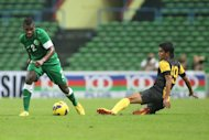 Azamuddin Akil of Malaysia (right) challenges Saudi Arabia's Mansour Alharbi during their football friendly match near Kuala Lumpur on March 17, 2013
