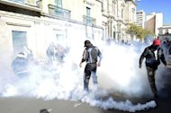 Bolivian policemen on strike are seen among tear gas thrown by themselves at Plaza Murilllo in La Paz. Rebel police clashed with pro-government supporters Monday outside Bolivia&#39;s presidential palace on the fifth day of a mutiny demanding better pay