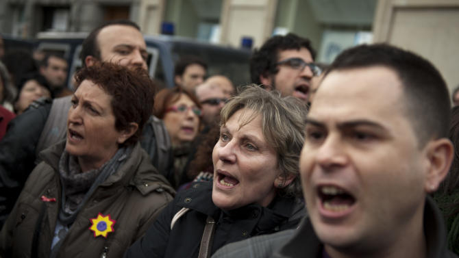 Demonstrators, some of them from the Platform of People Affected by Mortgages, a group campaigning to stop evictions, shout slogans against the government outside the Parliament as the Spanish Parliament considers whether to admit a popular petition to change mortgage laws and halt evictions of those unable to pay mortgages to a vote in Madrid, Tuesday, Feb. 12, 2013. The government agreed to consider changes to the law on mortgages after pressure from opposition parties and a growing public outcry, including a petition that was signed by 1.4 million people – enough signatures to force Parliament to discuss alterations to the law in a special session. (AP Photo/Daniel Ochoa de Olza)