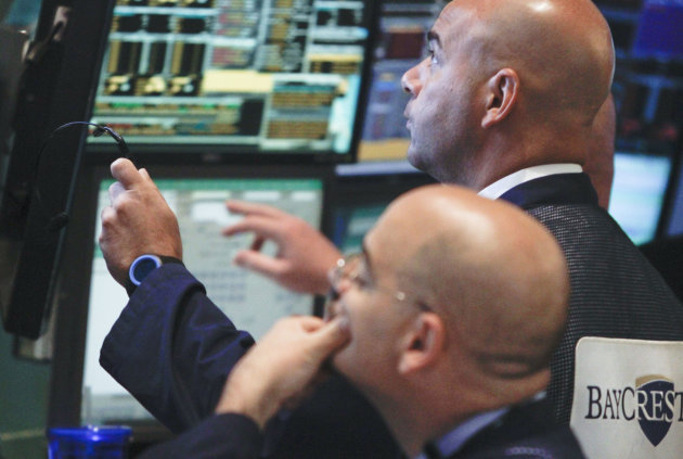 Traders work at the start of early trading at the New York Stock Exchange on Tuesday, July 10, 2012. Stocks are opening higher after European leaders accelerated a plan to shore up Spain's troubled banks. (AP Photo/Bebeto Matthews)