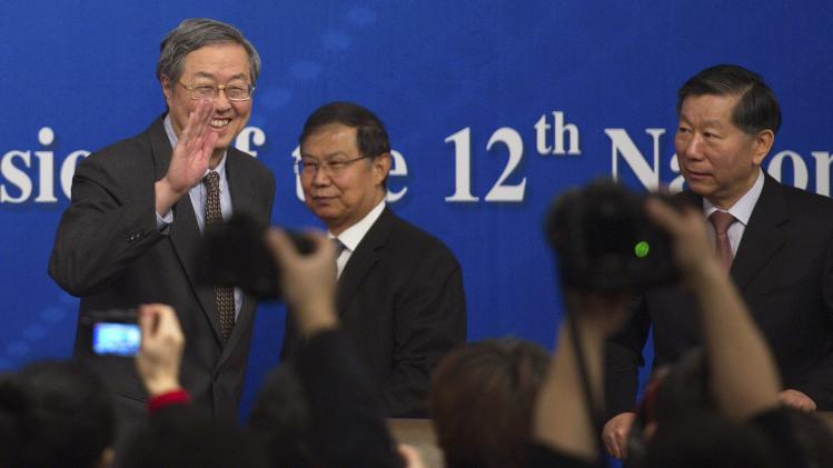 China's central bank governor Zhou waves to journalists during a news conference as part of the NPC in Beijing