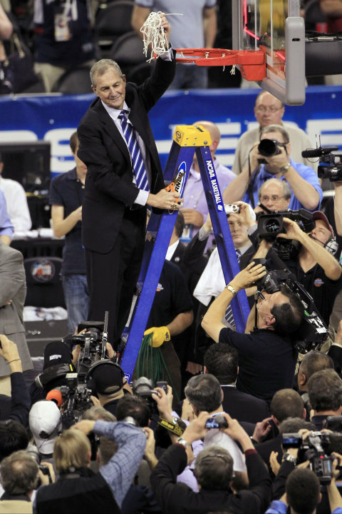 FILE - In this April 4, 2011, file photo, Connecticut head coach Jim Calhoun holds the net after his team defeated Butler 53-41 to win the men's NCAA Final Four college basketball championship game in