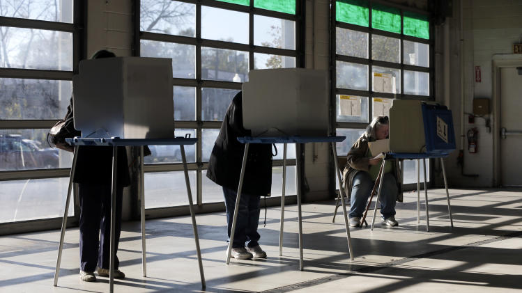 Voters fill out their ballots in a vehicle storage bay at Armory Garage, a Jeep, Chrysler, Dodge and Ram auto dealership on Election Day 2012 on Tuesday, Nov. 6, 2012, in Albany, N.Y. After a grinding presidential campaign President Barack Obama and Republican presidential candidate, former Massachusetts Gov. Mitt Romney, yield center stage to American voters Tuesday for an Election Day choice that will frame the contours of government and the nation for years to come. (AP Photo/Mike Groll)