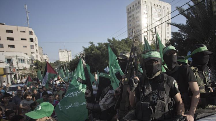 Palestinian masked Hamas gunmen hold their guns as they attend a rally in Gaza City, Wednesday, Aug. 27, 2014. An open-ended cease-fire between Israel and Palestinian militants in the Gaza Strip was holding Wednesday.(AP Photo/Khalil Hamra)