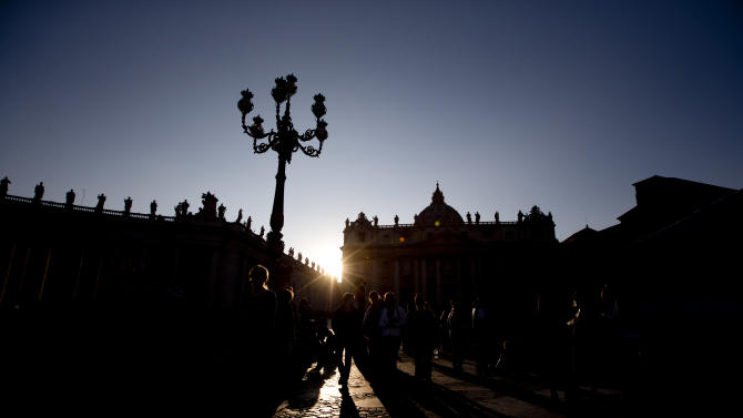 Tourists walk in the square as the sun sets behind the statues on top of the Bernini colonnade in St. Peter Square, at the Vatican, Monday, March 4, 2013. Cardinals from around the world have gathered inside the Vatican for their first round of meetings before the conclave to elect the next pope, amid scandals inside and out of the Vatican and the continued reverberations of Benedict XVI's decision to retire. (AP Photo/Andrew Medichini)
