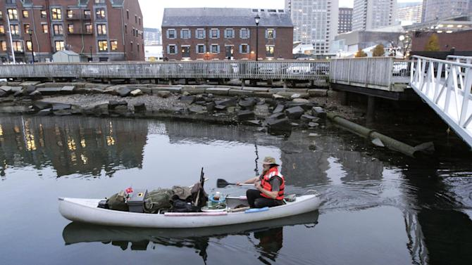 Michael Richard Smith pilots his canoe in Boston Harbor, in Boston, Tuesday, Dec. 4, 2012. The 49-year-old Maine native said Tuesday that he's been paddling the waters of metro Boston since at least late summer with all of his possessions aboard a 14-foot, 40-year-old aluminum canoe that he patches with duct tape when necessary. (AP Photo/Steven Senne)