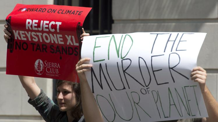 """Protesters demonstrate outside an event where Canadian Prime Minister Stephen Harper was to speak at the Council on Foreign Relations in New York, Thursday, May 16, 2013. Harper said Thursday that a controversial oil pipeline from his country to the U.S. Gulf Coast """"absolutely needs to go ahead"""" and warned that the oil will be transported through America one way or another. (AP Photo/The Canadian Press, Adrian Wyld)"""