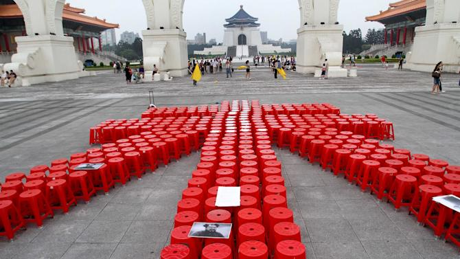 """Hundreds of red plastic chairs are arranged to form one of Chinese characters of Chinese artist and activist Ai Weiwei's name to support him on the Liberty Square in front of the Chiang Kai-shek Memorial Hall in Taipei, Taiwan, Saturday, June 4, 2011. Chinese police detained Ai on April 3, 2011 without laying any official charges and the authorities alleged a company controlled by Ai evaded """"huge amount"""" of tax. (AP Photo/Chiang Ying-ying)"""