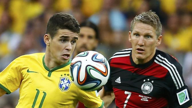 Brazil's Oscar fights for the ball with Germany's Schweinsteiger during their 2014 World Cup semi-finals at the Mineirao stadium in Belo Horizonte