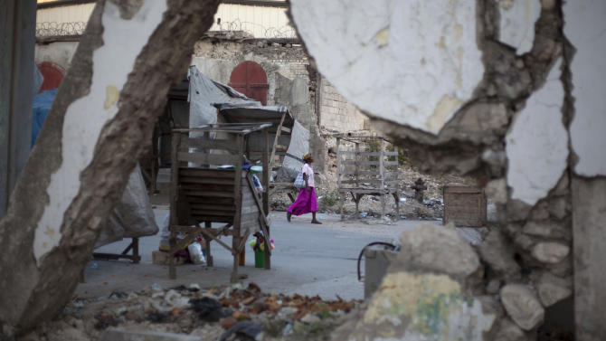 A woman walks past buildings damaged by the 2010 earthquake in downtown Port-au-Prince, Haiti,  Wednesday, Jan. 9, 2013. Governments around the world have spent about half of the $5.3 billion pledged for Haitian reconstruction. Most of the rubble is gone; there are two new sewage treatment plants north of the capital and a few homes. Many Haitians had expected more progress by now. (AP Photo/Dieu Nalio Chery)