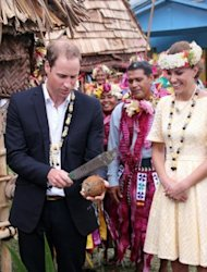 Prince William breaks open a coconut next to his wife Catherine during their visit to Tuvalu on September 18. Their low-key tour was carried out against a backdrop of high-powered legal action in Europe
