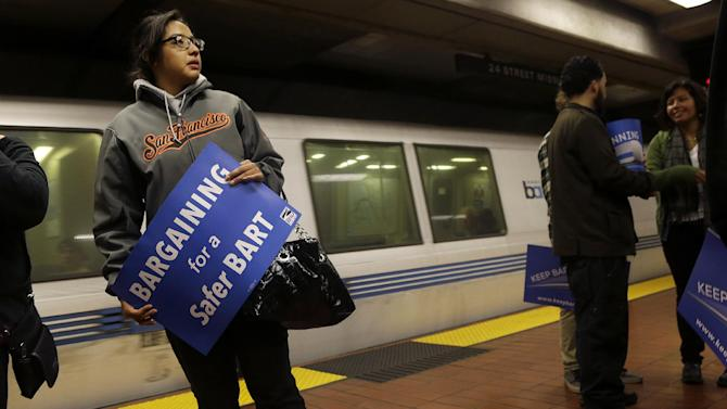 FILE - In this Tuesday, June 25, 2013 file photo, Jeanette Sanchez holds a sign supporting Bay Area Rapid Transit workers as she waits for a train at the 24th Street Mission station in San Francisco. Early Monday, July 1, 2013, two of San Francisco Bay Area Rapid Transit's largest unions went on strike after weekend talks with management failed to produce a new contract. (AP Photo/Jeff Chiu)