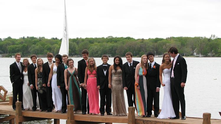 In this photo provided by Susan Orne, a group of 18 Wisconsin high school students poses for a photo prior to their prom on a pier in Oconomowoc, Wis. on Saturday, May 5, 2012, before a section gave way, dropping about half of them into the waist-deep water of a lake. The kids sloshed toward one student's home, where they all broke out the towels, hair dryers and clothes dryers. Everyone made the big event, and Orne says the incident has provided them a memory they'll all enjoy at their 50th reunion. (AP Photo/Courtesy Susan Orne)