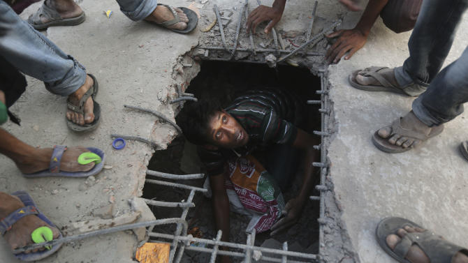 A Bangladeshi rescuer looks out from a hole cut in the concrete at the site of a building that collapsed Wednesday in Savar, near Dhaka, Bangladesh, Thursday, April 25, 2013. By Thursday, the death toll reached at least 194 people as rescuers continued to search for injured and missing, after a huge section of an eight-story building that housed several garment factories splintered into a pile of concrete.(AP Photo/Kevin Frayer)