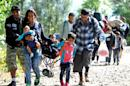 A migrant family walks toward the border after arriving at the railway station of Botovo, near the Croatian-Hungarian border, on September 21, 2015
