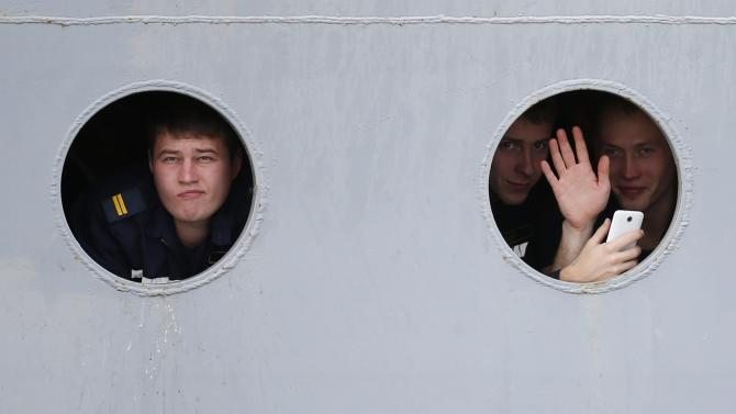 Russian sailors look through the portholes of the Russian Navy frigate Smolny as they leave the STX Les Chantiers de l'Atlantique shipyard site in Saint-Nazaire