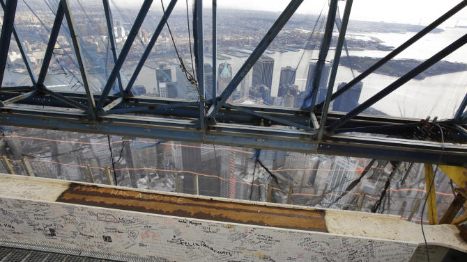 A steel beam, bearing the signatures of hundreds of workers and President Barack Obama, is in place on the 104th floor of One World Trade Center, Tuesday, Dec. 11, 2012 in New York.  A 408-foot spire is expected to rise on top of the tower by spring. (AP Photo/Mark Lennihan)