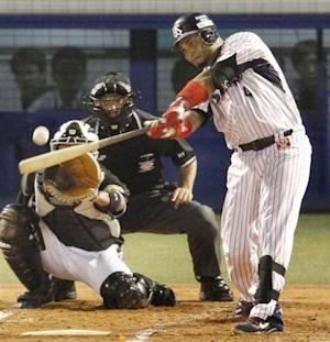 Tokyo Yakult Swallows' Wladimir Balentien hits his 56th homer to break Japan's single-season, off Hanshin Tigers' Daiki Enokida in the first inning of their regular season baseball game in Tokyo