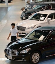 A customer looks at Nissan vehicles at the company&#39;s showroom in Yokohama, suburban Tokyo on Thursday. Nissan says its business in the debt-hit European market has taken a beating, with sales down 1.7%