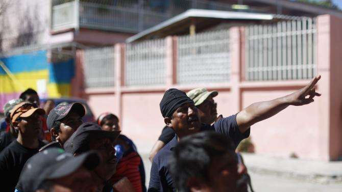 Members of the Community Police of the FUSDEG look to a hill, where they said they saw suspected members of a local gang, in the village of Petaquillas