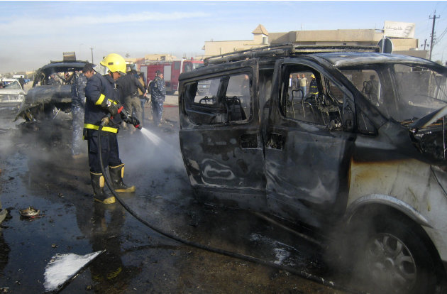 An Iraqi firefighter hoses down a burned bus after a car bomb attack in Kirkuk, 290 kilometers (180 miles) north of Baghdad, Iraq, Thursday, Feb. 23, 2012. A rapid series of attacks spread over a wide
