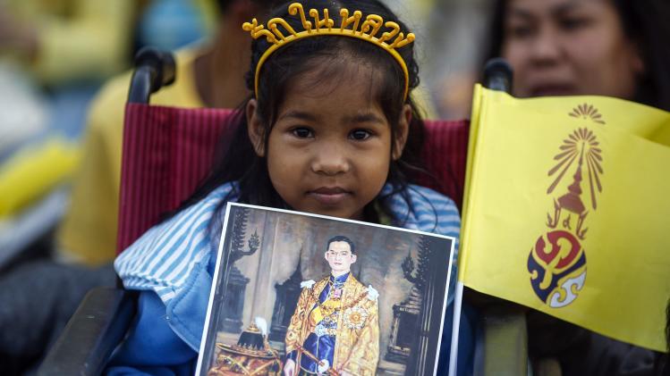 Girl holds a picture of Thai King Bhumibol as well-wishers gather to celebrate his 86th birthday near Klai Kangwon Palace in the resort town of Hua Hin