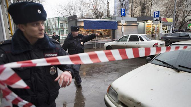 Police set a crime scene tape near a suspicious car, background, in Moscow, Russia, Saturday, Feb. 28, 2015. Russia's top investigative body said Saturday it is looking into several possible motives for the killing of prominent opposition figure Boris Nemtsov, including an attempt to destabilize the state, Islamic extremism, the Ukraine conflict and his personal life. (AP Photo/Denis Tyrin)