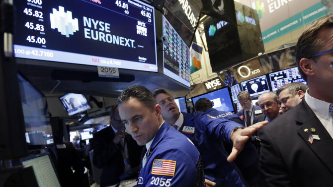 Specialists Jason Hardzewicz, left, and Patrick Murphy, second left, handle the final trades of the NYSE Euronext stock on floor of the New York Stock Exchange, Tuesday, Nov. 12, 2013. The ICE and NYSE Euronext tie-up will close Wednesday. (AP Photo/Richard Drew)