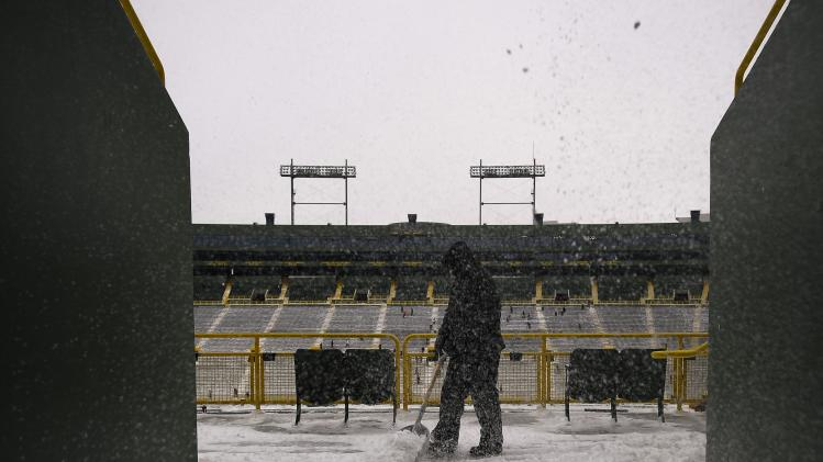 Snow is dropped from above as a paid volunteer clears snow from the bleachers at Lambeau Field in Green Bay