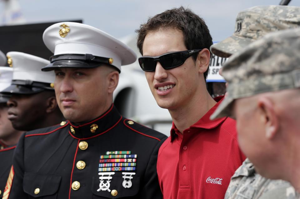 NASCAR driver Joey Logano, center, poses with Marines,, loeft, and soldiers, right, during a news conference for the NASCAR Coca-Cola 600 auto race on May 26 in Charlotte, N.C., Tuesday, April 23, 2013. (AP Photo/Chuck Burton)