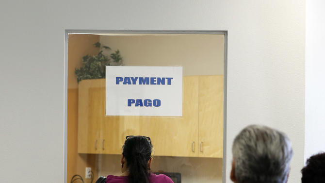 In this July 12, 2012 photo, patients stand in line to make payments at Nuestra Clinica Del Valle in San Juan, Texas.  About 85 percent of those served at the clinic are uninsured. Texas already has one of the nationís most restrictive Medicaid programs, offering coverage only to the disabled, children and parents who earn less than $2,256 a year for a family of three. Without a Medicaid expansion, the stateís working poor will continue relying on emergency rooms _ the most costly treatment option _ instead of primary care doctors. The Texas Hospital Association estimates that care for uninsured patients cost hospitals in the state $4.5 billion in 2010. (AP Photo/Eric Gay)