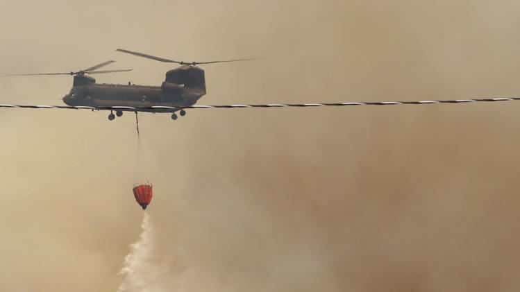 A helicopter drops water on a large grass fire east of 120th near Cemetery Road on Friday, Aug. 3, 2012, east of Norman, Okla.  A wildfire stirred by high winds sweeping through rural woodlands just south of the Oklahoma City area has set at a number of homes on fire.  (AP Photo/The Oklahoman, Steve Sisney) TABLOIDS OUT