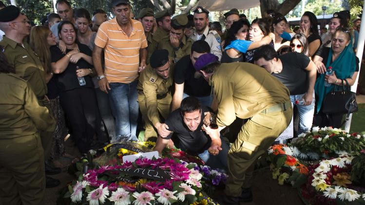 The brother of Israeli soldier Daniel Kedmi mourns over his grave during his funeral in Tel Aviv