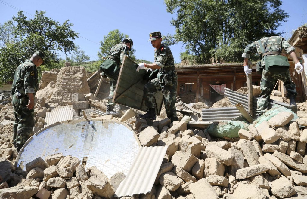 Paramilitary policemen search for victims amongst collapsed houses after a 6.6 magnitude earthquake hit Minxian county
