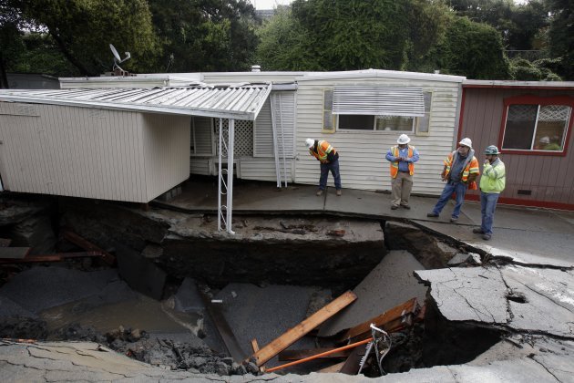Workers inspect a sink hole caused by flooding at the Pacific Cove Mobile Home Park in Capitola, Calif., Friday, March 25, 2011.   A powerful storm swept across California flooding part of Capitola, i