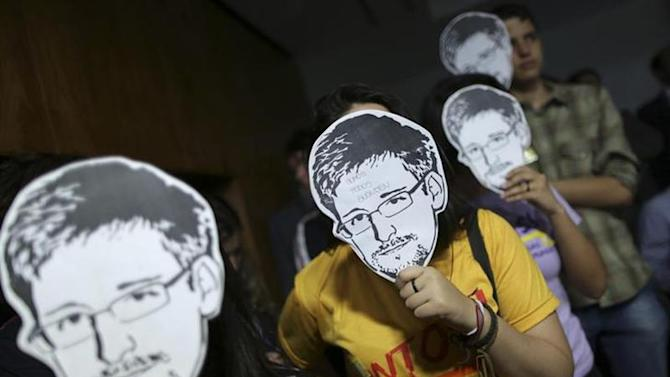 People use masks with pictures of former NSA contractor Edward Snowden masks during the testimonial of Glenn Greenwald, the American journalist who first published the documents leaked by Snowden, before a Brazilian Congressional committee on NSA's surveillance programs, in Brasilia August 6, 2013. REUTERS/Ueslei Marcelino/Files