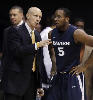 Xavier coach Chris Mack talks with Dezmine Wells during the first half of an NCAA college basketball game against Butler on Wednesday, Dec. 7, 2011, in Indianapolis. (AP Photo/Darron Cummings)