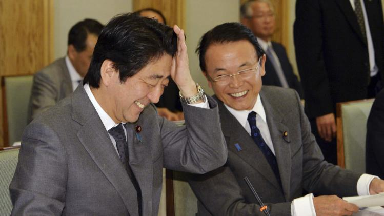 Japan's PM Abe smiles with Finance Minister Aso before a meeting of the economy and fiscal policy council in Tokyo