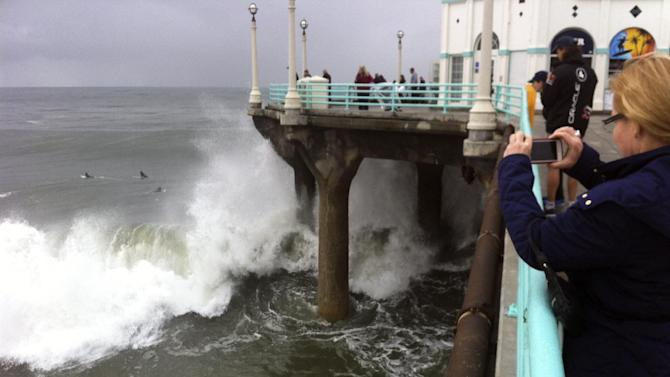 Big surf pounds the pier at Manhattan Beach, Calif., on Sunday, March 2, 2014, in the aftermath of a powerful Pacific storm. Showers from residual moisture fell in the region, but forecasters said a developing ridge of high pressure would bring a period of dry weather. (AP Photo/John Antczak)