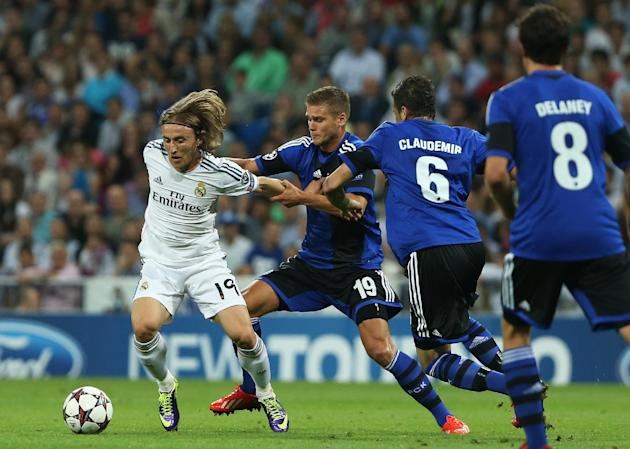 Real Madrid's Luka Modric from Croatia, left, duels for the ball with FC Copenhagen's Rurik Gislason, second left, during the Champions League group B soccer match between Real Madrid and FC Copenhage