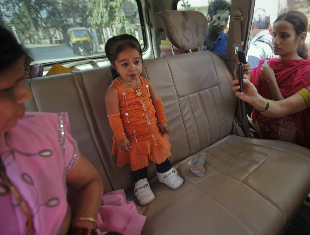 Amge, the world's shortest woman, stands on the backseat of a car as people take pictures outside while campaigning for MNS for the upcoming municipal elections in Mumbai